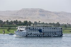 A floating hotel moves along the River Nile in Egypt from Luxor towards the Esna Lock. Stock Photo