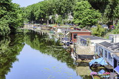 Floating houses. View of floating houses built on the long of a calm canal due to the global warming and the elevation of the water level around the world Stock Photo