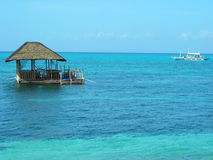 Floating hut at tropical island. Beautiful turquoise seas off the shores of Malapascua island in the Philippines, with floating hut royalty free stock photos