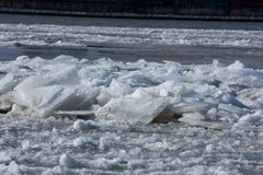 Floating Ice Blocks on the River. Frozen, snow capped ice blocks floating down the river on a cold winter afternoon Stock Image