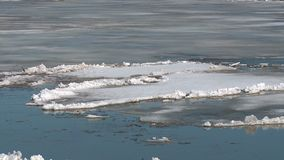 Ice floes float on the river in the spring during the ice drift. Floating ice floes on the river in the spring during the ice drift stock video footage