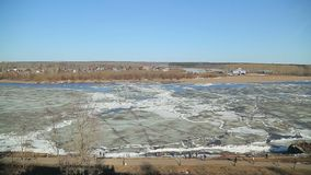 Ice floes float on the river in the spring during the ice drift. Floating ice floes on the river in the spring during the ice drift stock footage