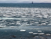 Floating ice with oil rig in the background Royalty Free Stock Image
