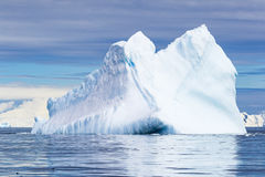 Floating Iceberg with blue sky, water and light Stock Photography