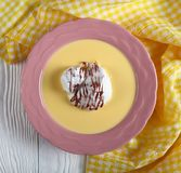 A floating island or birds milk. Consisting of meringue floating on creme anglaise and drizzled with chocolate ganache in pink plate with kitchen napkin on Royalty Free Stock Photos