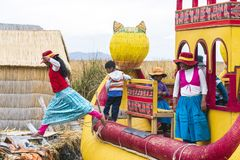 Floating Islands children. PUNO, PERU - NOVEMBER 5: child girl jumping from big cane boat to floating island at lake Titicaca near Puno, Peru on November 5, 2018 royalty free stock photography