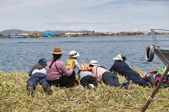 Floating Islands family. PUNO, PERU - NOVEMBER 5: local people relax in front of water on floating Uros islands at lake Titicaca near Puno, Peru on November 5 stock photos