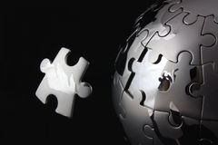 Floating last jigsaw piece. Chrome jigsaw peice floating near a globe puzzle stock images