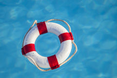Floating lifesaver. Floating red and white colored lifesaver in the swimming pool, concept for security and help Stock Photography