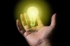 Floating light bulb with human hand. Stock Image