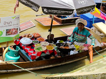 Floating market female hawker. A female hawker is sitting on her boat at Amphawa floating market, waiting for customers Royalty Free Stock Photos