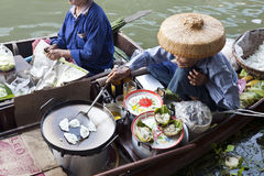 Floating Market Food Seller. An old Thai woman fries traditional Thai snaks on her boat at Damnoen Saduak floating market near Bangkok, Thailand Royalty Free Stock Photo
