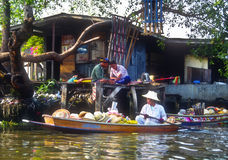 Floating Market Merchant, Thailand. A woman in a small boat, who sells hats and umbrellas at a local floating market, paddles her way home on the river, passing Royalty Free Stock Image