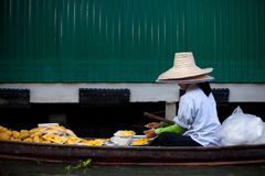 The floating market in Thailand. Local Thai woman sells fruits at Damnoen Saduak floating market in Bangkok, Thailand Stock Photos