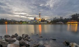Floating mosque during sunset with dramatic clouds. View of Floating mosque also known as Tengku Zaharah mosque with a majestic clouds during sunset near the Royalty Free Stock Image
