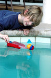 Floating my boat. A boy plays with his homemade boat in the swimming pool stock photography