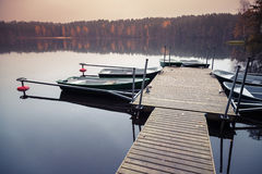 Floating pier with moored row boats, still lake Stock Photography