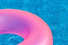 Floating pink ring on blue water swimpool. royalty free stock photos
