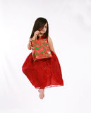 Floating Present. Pretty little girl in red dress floating with Christmas gift Stock Image