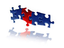 Floating puzzle pieces. Floating red and blue puzzle pieces over a reflective white background Royalty Free Stock Photo