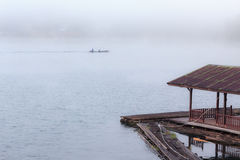 Floating raft house on river with foggy and long tail boat on background. Royalty Free Stock Images