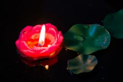 Floating red candle in a pond. A floating red candle amonst some lily pads in a pond Stock Photo