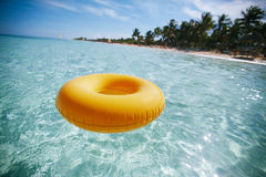 Floating ring on blue clear sea with beach Royalty Free Stock Images