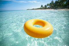 Floating ring on blue clear sea with beach Royalty Free Stock Photo