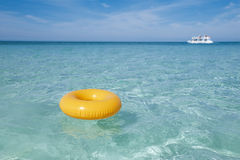 Floating ring on blue clear sea with white boat Royalty Free Stock Images