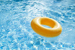 Floating ring on blue water swimpool with waves reflecting Stock Images