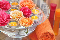 Floating roses and candles. Dish of glass and water with swimming roses and candles for aromatherapy, reiki, ayurveda Royalty Free Stock Images