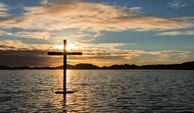 Floating Salvation. Black cross of salvation on a lake of water at sunset. And a spirit image of Jesus Stock Image