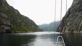 Floating in Trollfjord on yacht. Cloud over mountain far off. Enterance to Trollfjord on yacht in cloudy afternoon. Cloud over mountain far off stock footage