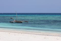 Small wooden fishing boat by white sand beach in Zanzibar stock photo