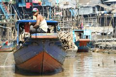 Floating village in Cambodia. By Tonle Sap lake. Man sitting on the boat swimming toards the lake Tonle Sap, which is the source of food for the people in the stock photography