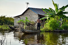 Floating village house with a man near Siem Reap in Cambodia. Floating village houses near Siem Reap in Cambodia. The houses are relocated a few times each year royalty free stock photography
