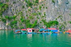 Floating village and rock islands in Halong Bay Stock Photos