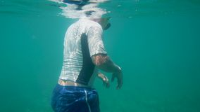 Floating on the water in a swimming gear. A medium shot of a man floating on the sea wearing a swimming gear stock video