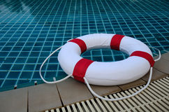 Floating white ring on edge of swimpool. Royalty Free Stock Images