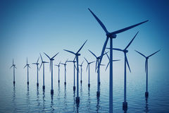 Floating wind turbines during hazy day. Royalty Free Stock Photo