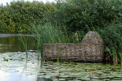 Floating wooden cradle on water. Wooden cradle basket floating on water with lily pads in Kinderdijk Netherlands stock image