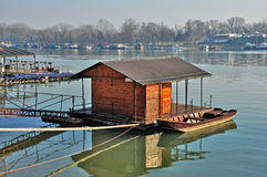 Floating wooden house with boat Royalty Free Stock Photo