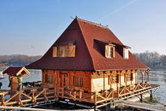 Floating wooden house with boat Royalty Free Stock Photography