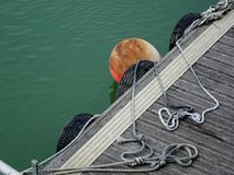 Floating Wooden Jetty with Fenders. A Jetty Walkway, Showing a Buoy and Protection Tyre Fenders with Rope Slip knots and Tails on Wooden Non-Slip Planks royalty free stock image