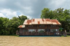 Floating wooden Thai house near river. Traditional riverside floating wooden Thai house at Bang Pakong River, Chachoengsao, Thailand. Local lifestyle with Stock Image