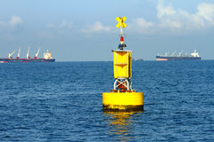 Floating yellow navigational buoy on blue sea Royalty Free Stock Photo