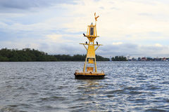 Floating yellow navigational buoy on blue sea Royalty Free Stock Image