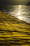 Floating yellow piers on water lighting by sunset. Floating piers wrapped in yellow cloth are carried on the water. Water is calm and have small waves. Far from royalty free stock image