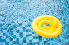 Floating yellow ring on blue water swimpool with waves reflectin Stock Photography