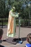 Floating Yoda street entertainer on the tow path of the Thames in London. While an audience of tourists look on Royalty Free Stock Photography